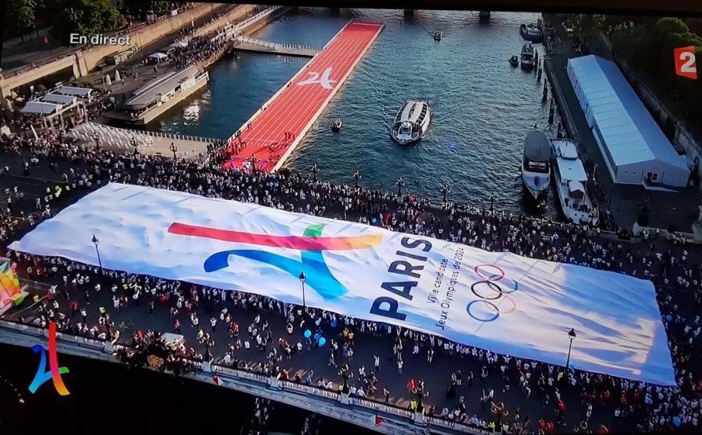 この日のイベントは、パリ・オリンピック2024と書いた巨大なメッセージ・カーペットをアレキサンダー大王橋にかけた。